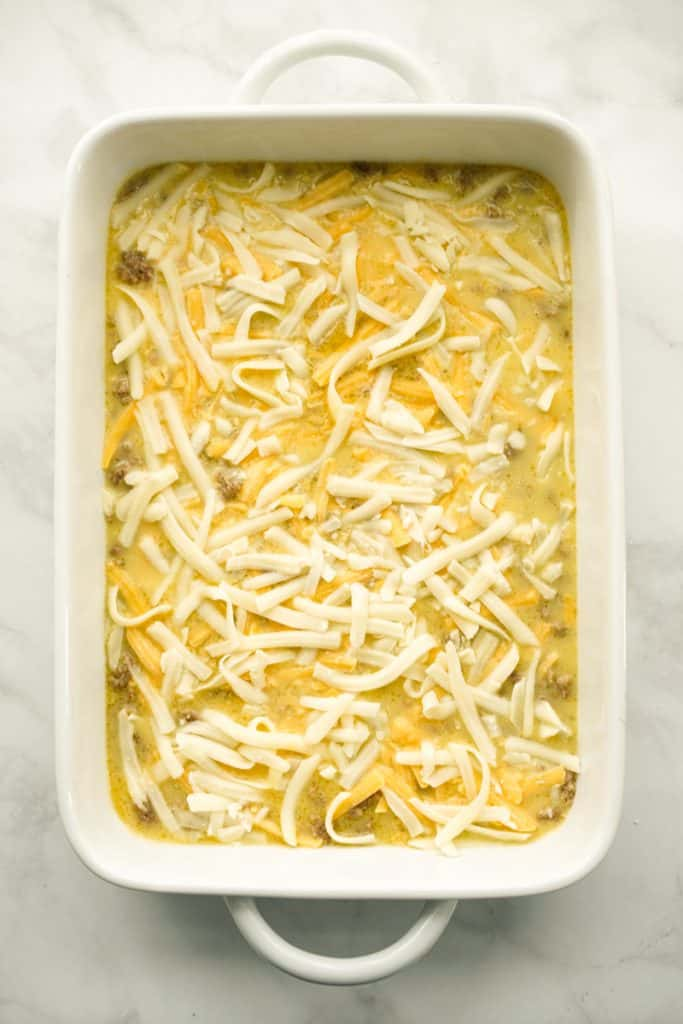 Sausage, eggs and cheese in a casserole prior to baking