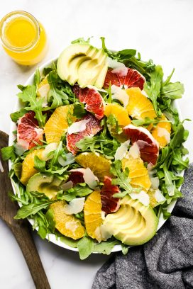 An oval bowl of arugula topped with oranges, avocados and parmesan cheese
