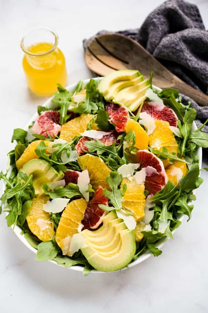 A bowl of arugula salad with avocados, oranges, blood oranges and parmesan on top