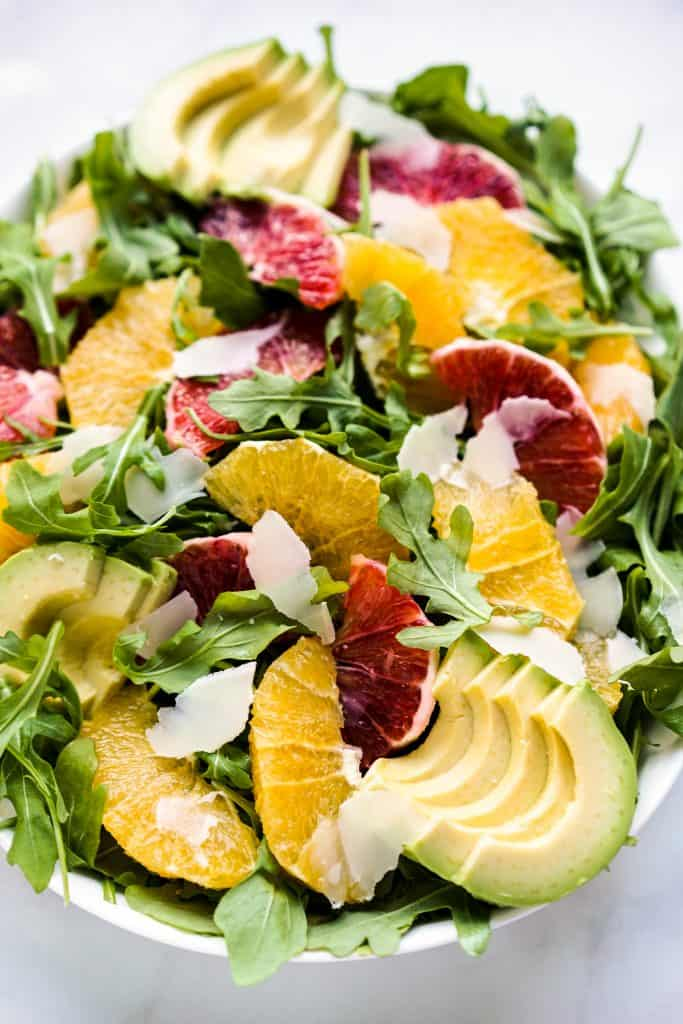 closeup of a bowl of arugula topped with oranges, avocados and parmesan