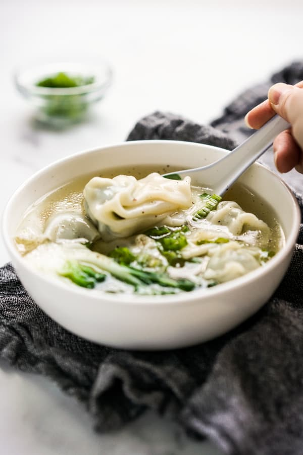 PIcking up a wonton from a bowl of wonton soup