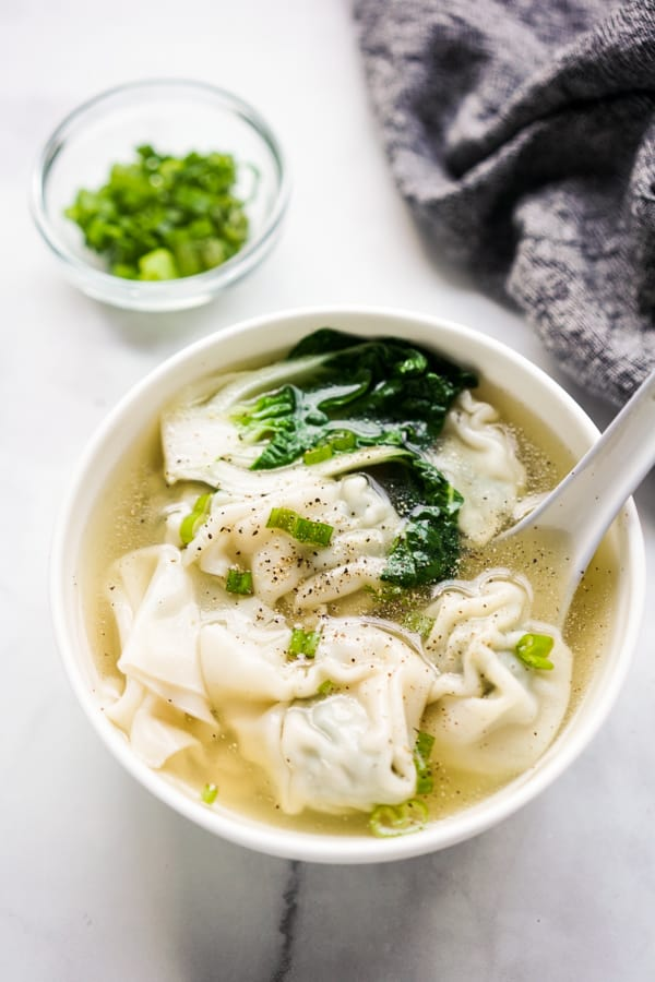 A bowl of wonton soup with spoon in it