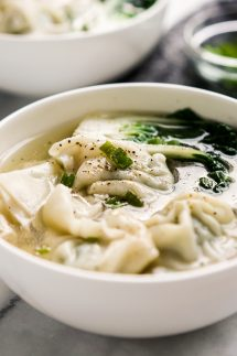 A bowl of soup with wontons and bak choy