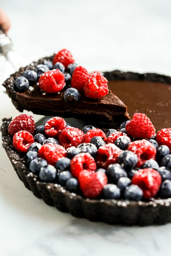 Cutting out a slice of chocolate tart topped with blueberries and raspberries