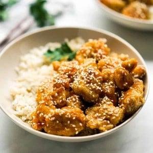 Closeup of a bowl of crispy honey sesame chicken
