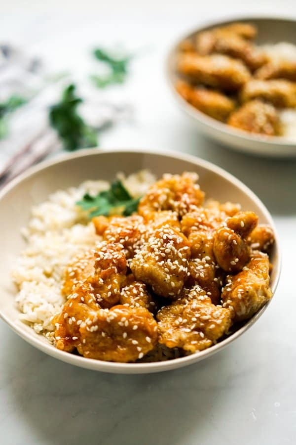 A bowl of rice topped with sticky honey sesame chicken