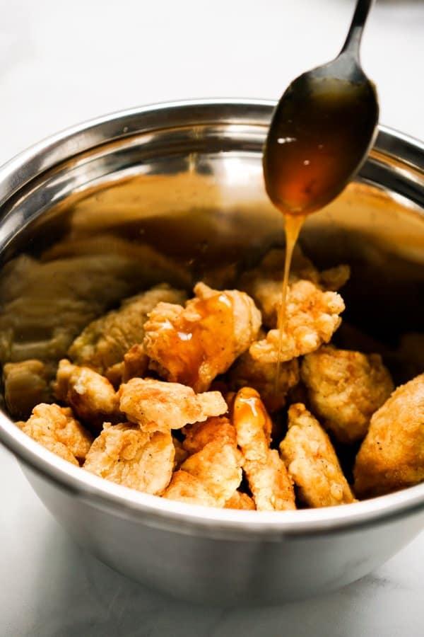 Drizzling honey sesame sauce onto breaded chicken