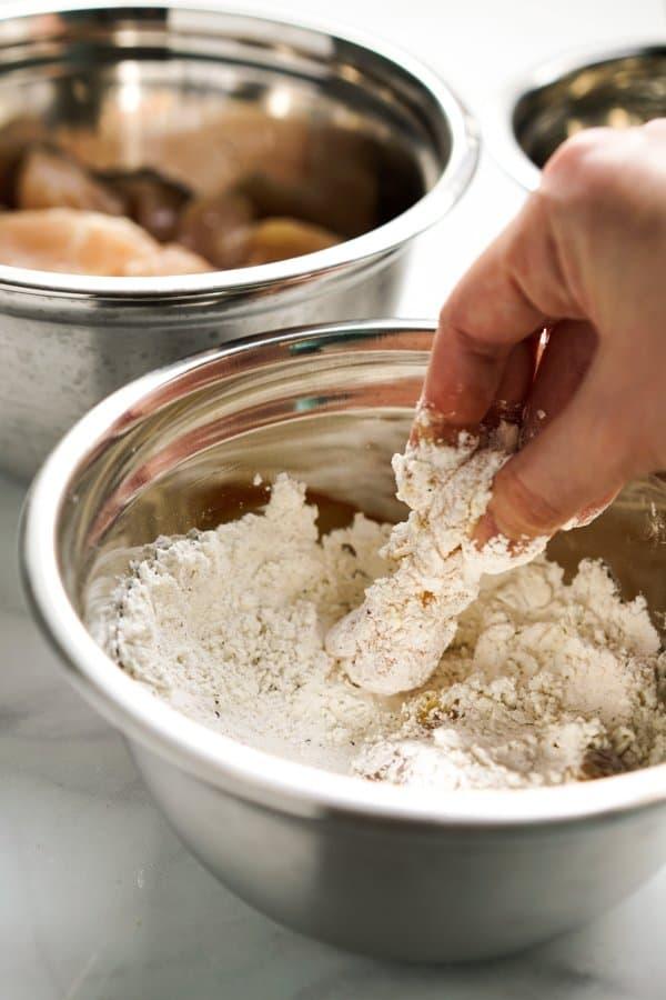 Dipping chicken into flour mixture