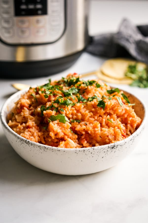 A bowl of Mexican rice with an Instant Pot behind it