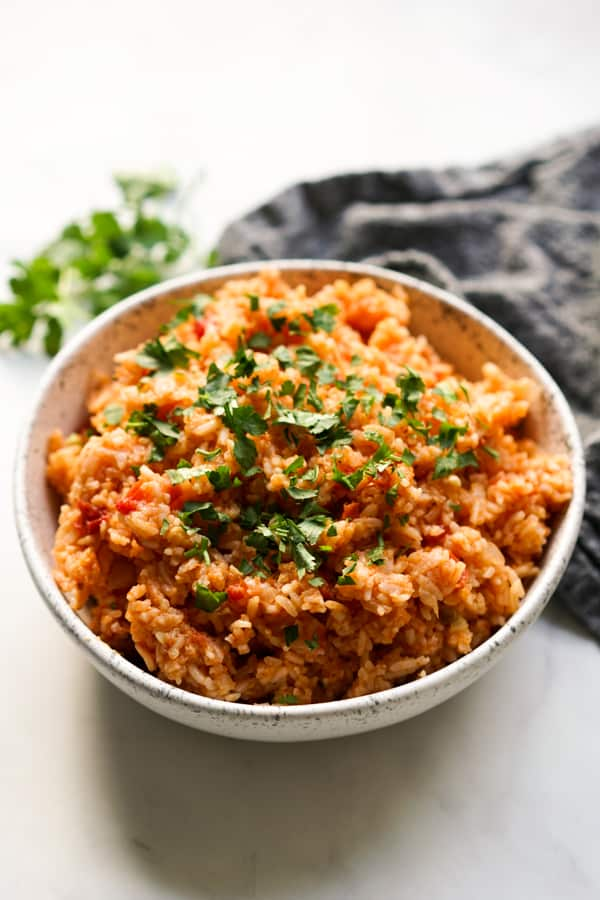 A bowl of seasoned Mexican rice topped with chopped cilantro