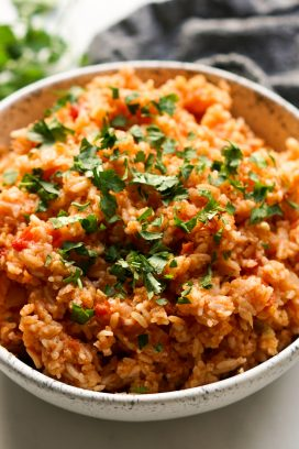 A bowl of seasoned mexican rice with small chunks of tomatoes
