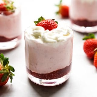 A jar of strawberry mousse with whipped cream and fresh strawberry