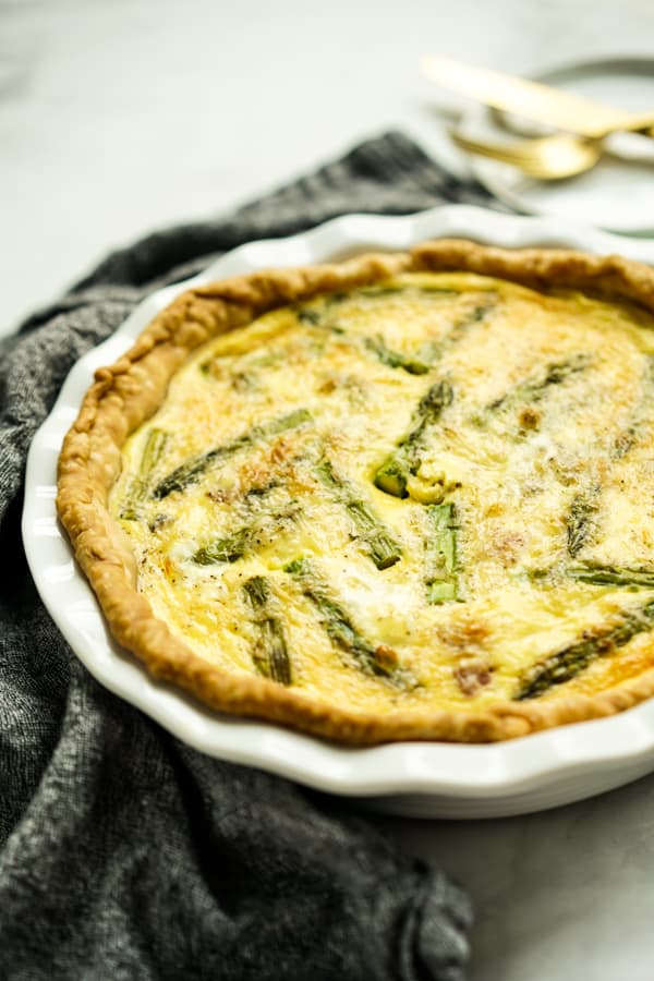 A round plate of quiche with asparagus