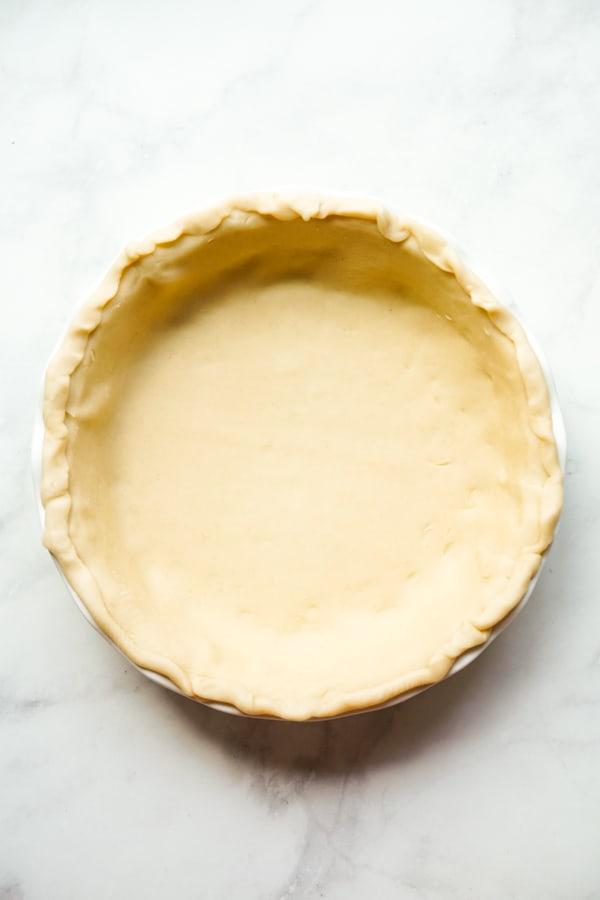 Unbaked pie crust on a round pie pan