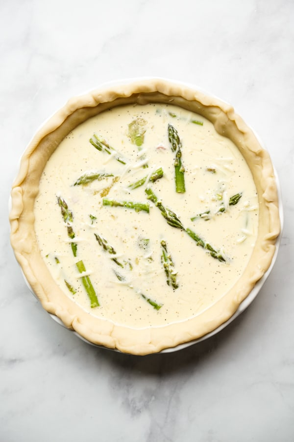 Unbaked pie crust topped with asparagus, ham, eggs and cheese