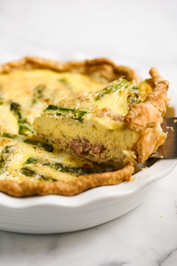 Lifting up a slice of Asparagus and Ham quiche