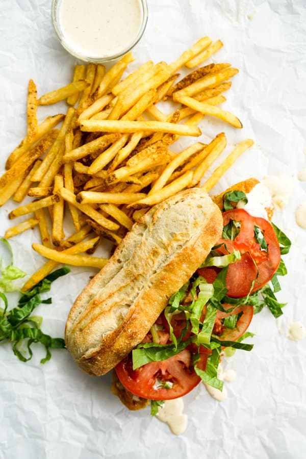 French baguette with fried fish, tomatoes and lettuce, French fries, and remoulade