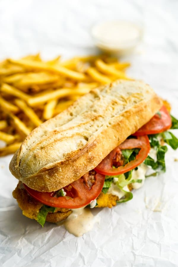 French baguette loaded with fried fish, lettuce, tomatoes, and remoulade