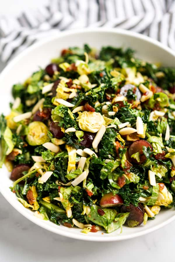 Close up of Brussels sprouts, kale tossed with grapes and slivered almonds