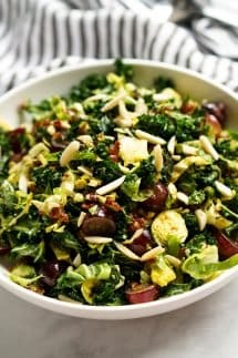 A bowl of Kale and Brussels Sprouts Salad topped with almonds and bacon vinaigrette