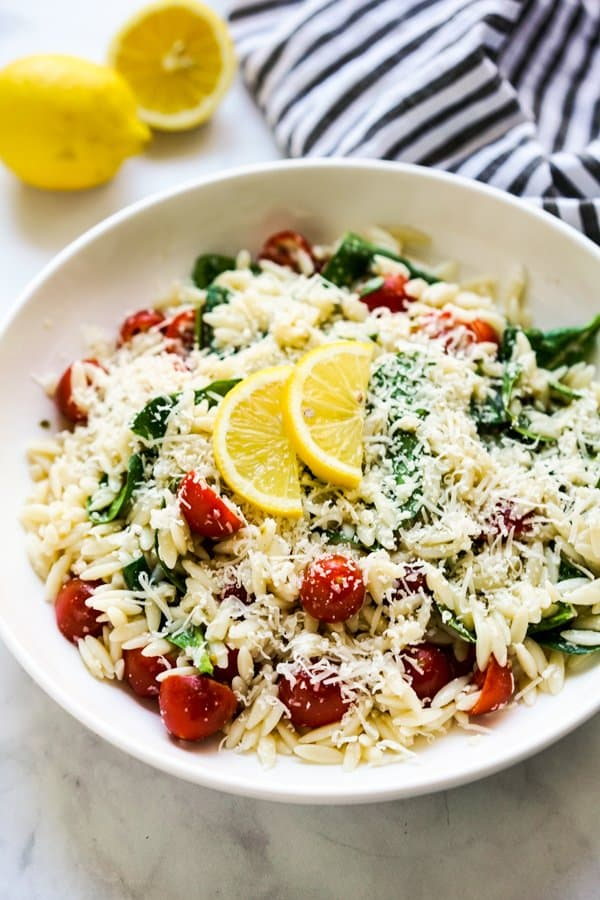 A bowl of lemony orzo pasta topped with parmesan and lemon slices