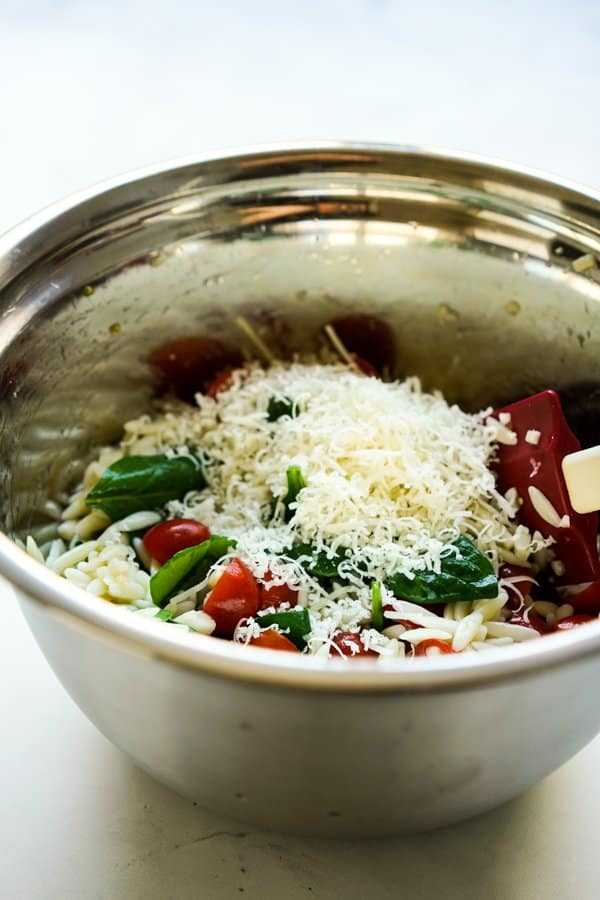 A bowl of orzo salad with grated parmesan cheese on top