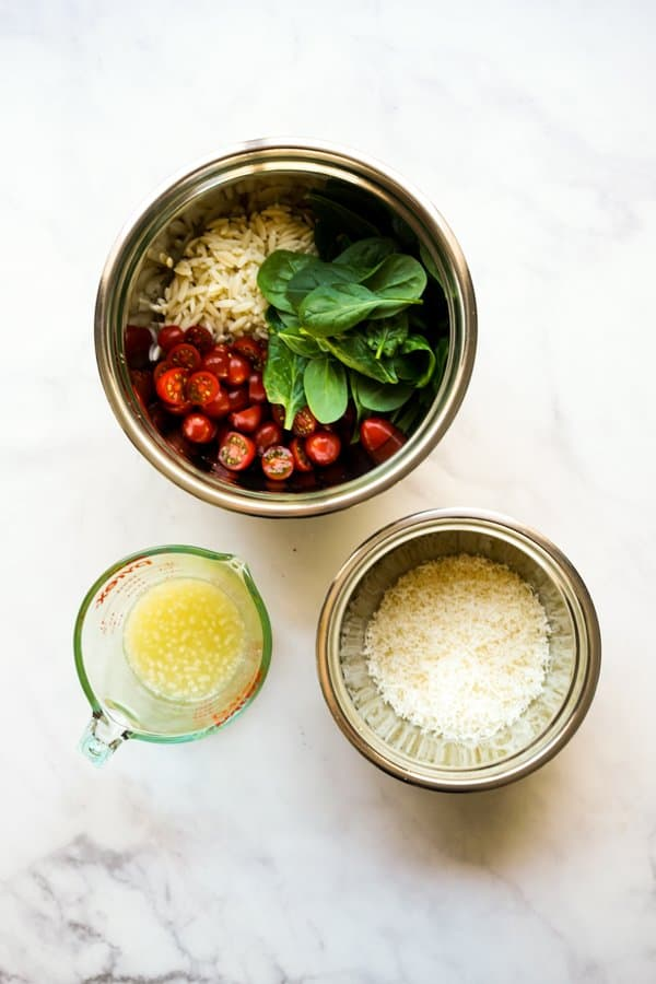 A bowl of pasta with cherry tomatoes and spinach, a bowl of shredded parmesan cheese, and a cup of lemon juice