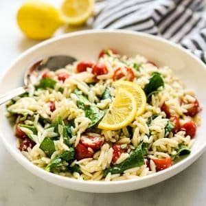 A bowl of orzo tossed with spinach, tomatoes, with lemon wedges on top