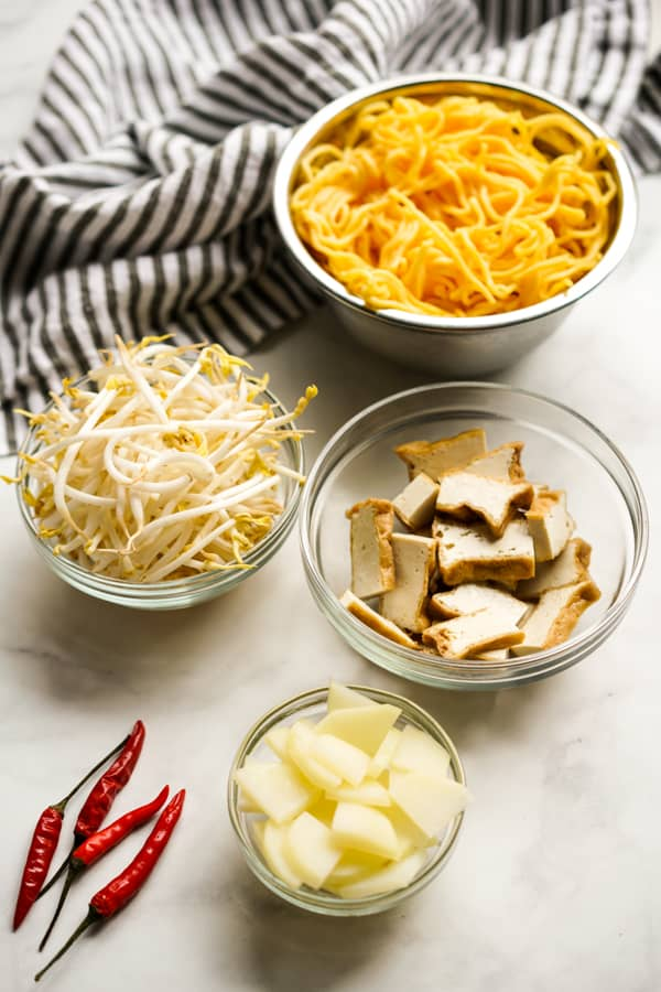 A bowl of yellow noodles, a bowl of beans sprouts, fried tofu, sliced potatoes and red chilies