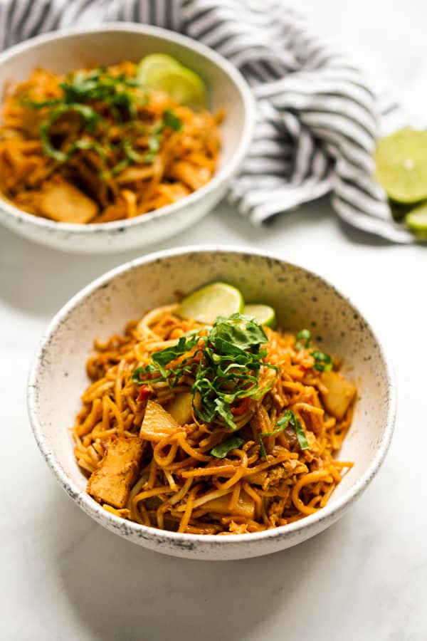 Two bowls of Mee Goreng Mamak style garnished with lettuce and lime wedges