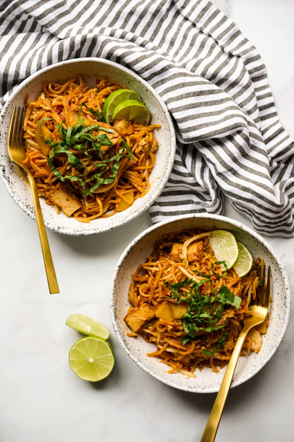 Two top down bowls of fried yellow noodles (Mee Goreng Malaysia)