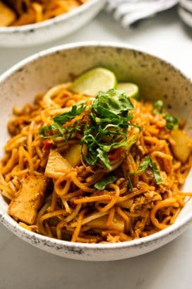 A bowl of Mee Goreng noodles with lettuce and lime garnish