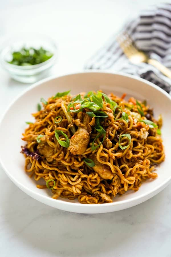 a plate of Tom Yum Fried Noodles topped with chicken and green onions