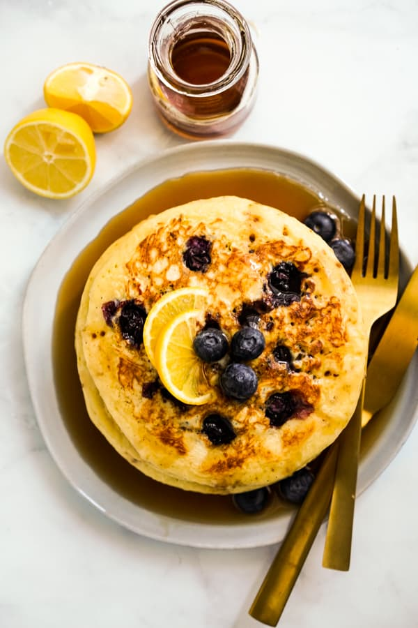 A plate of of stack of pancakes with lemons and blueberries, fork and knife on the side
