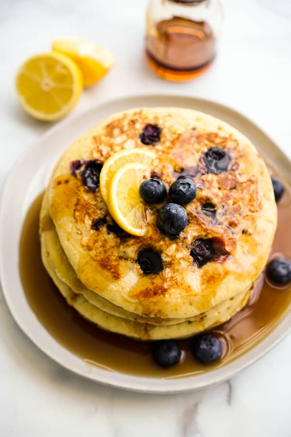 A stack of pancakes in maple syrup, along with blueberries and lemon slices