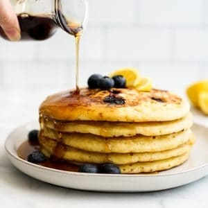 Pouring maple syrup onto Blueberry Lemon Ricotta Pancakes on a plate