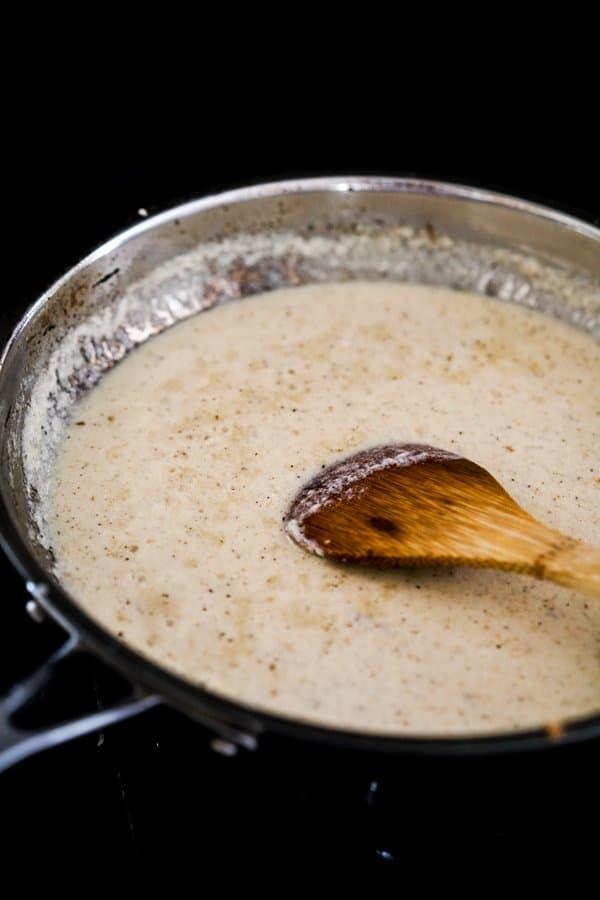 Cooking creamy lemon garlic sauce in skillet