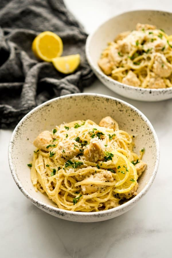 Two bowls of spaghetti pasta tossed with chicken pieces n creamy lemon sauce, topped with parmesan cheese