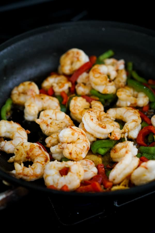 Searing shrimp and bell peppers in a skillet