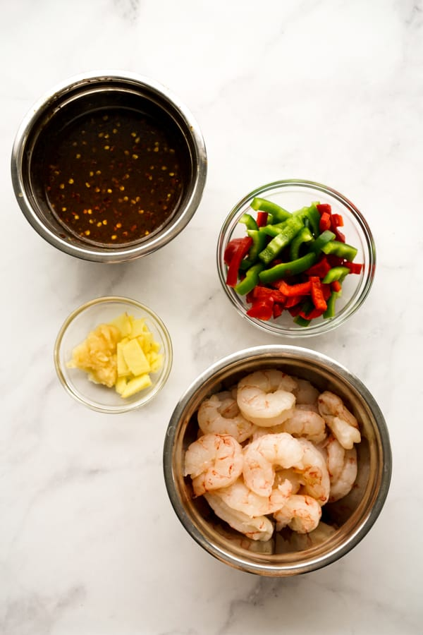 A bowl of raw shrimp, a bown of garlic and ginger, a bowl of red and green bell peppers, and a bowl of General Tso sauce