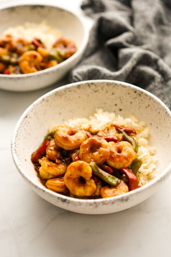 A bowl of rice topped with stir fried shrimp