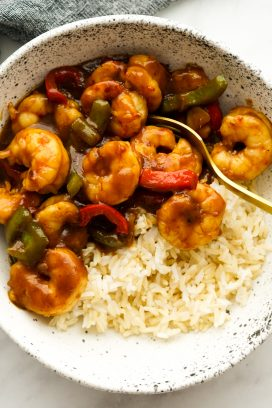 A bowl of shrimp stir fry with bell peppers and sticky sauce on top of rice