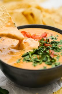 Dipping chip into a bowl of queso