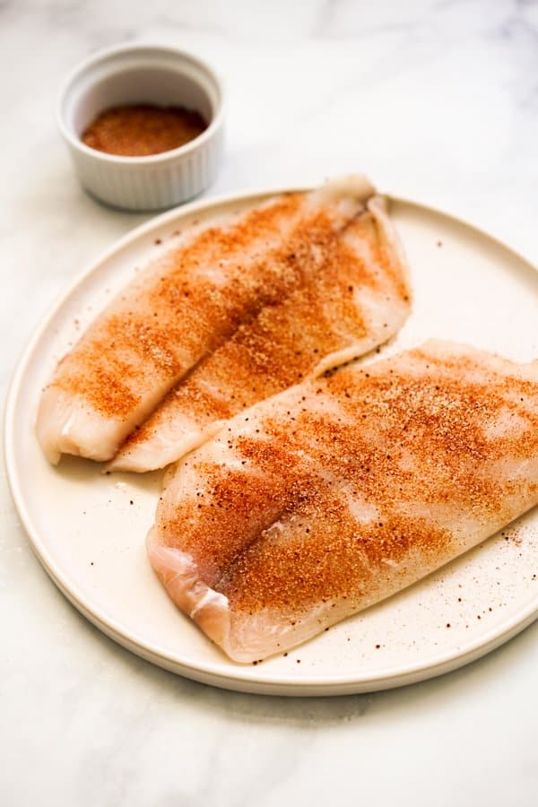 Uncooked tilapia fillets coated in spices