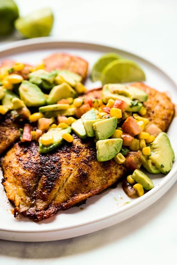 Seared tilapia fish with avocado and corn on top