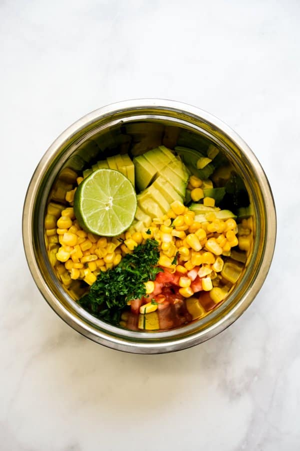 A mixing bowl with corn, tomatoes, cilantro, lime and avocados