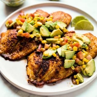 A plate of tilapia with avocado corn salsa