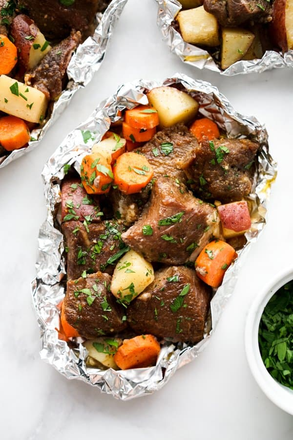 Steak, potatoes and carrots in foil pack