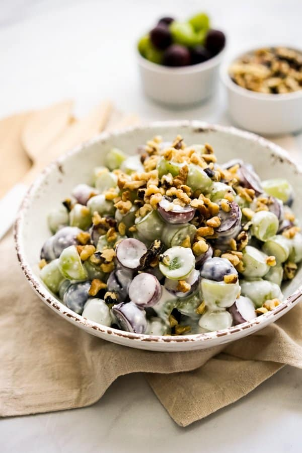 A bowl of grape salad with walnutes, with more grapes and walnuts in the background