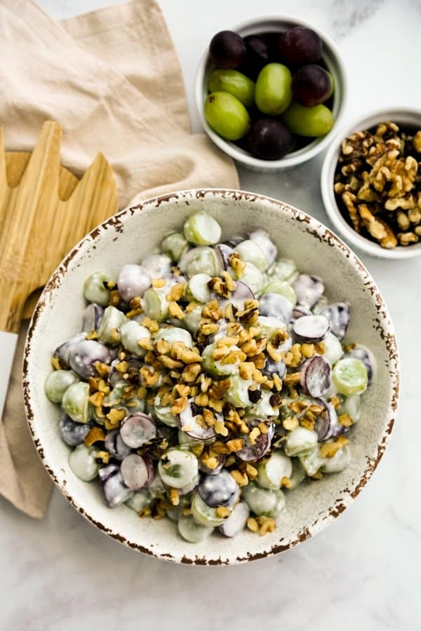 Top down view of a bowl of grapes salad tossed in creamy sauce, with walnuts on top
